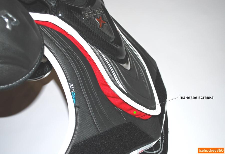 Центральный щиток соединен с защитной жилеткой тканью красного цвета.
